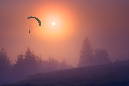 paraglide: Paraglide silhouette against the sunset sky, flying over the foggy mountain valley.