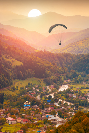 paraglide: Paraglide silhouette against the sunset sky, flying over the carpathian mountain village.