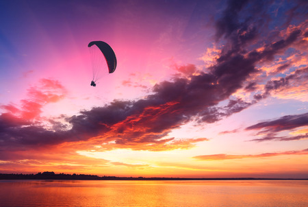 paraglide: Paraglide silhouette in a light of majestic sunset flying above the sea. Stock Photo