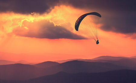 paraglide: Paraglide silhouette flying over the mountains. Beautiful rays of sun light on a foggy hills of Crimea mountain valley. Stock Photo
