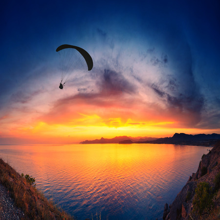 paraglide: Paraglide silhouette flying above the sea against colorful sunset background.