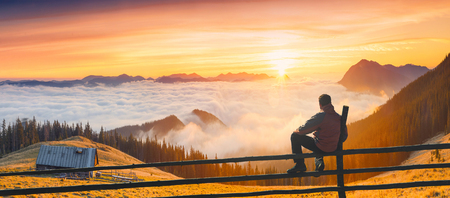 Man sitting on a wooden fence and enjoy majestic sunrise in a carpathian mountain valley with wooden house on a hill.