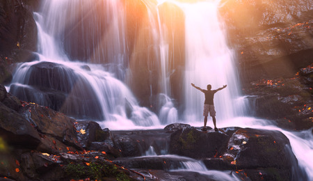 Man with raised hands standing on a waterfall in a Carpathian mountains. Ukraine, Europe. Фото со стока