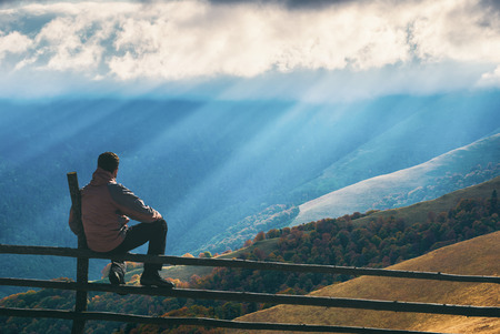 Hiker sitting on a wooden fence and enjoy rays of sunlight, shining through the clouds to the yellow autumn hills. Carpathian mountain valley.