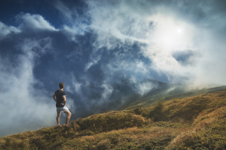 foggy hill: Hiker standing on a hill and enjoy sunrise in a carpathian foggy mountain valley.