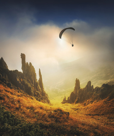 paraglide: Paraglide silhouette flying over the high mountain valley glowing by sunlight at sunrise. Dramatic and picturesque morning scene. Extreme sport. Stock Photo