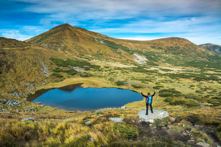 Tourist with backpack and trekking poles standing on a big stone near the mountain lake in a carpathian mountains