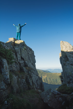 conquering adversity: Hiker standing on a cliffs edge with raised hands and enjoy the mountain valley.