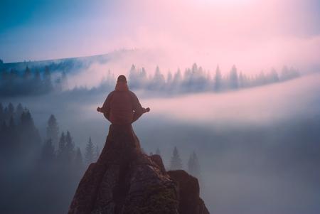 Human mediteren in zittende yoga-positie op de top van een berg in een mistige vallei. Zen, meditatie, vrede.