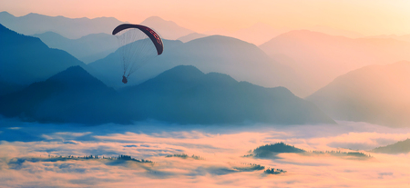 paraglide: Paraglide silhouette flying over the misty mountain valley in a light of sunrise. Stock Photo