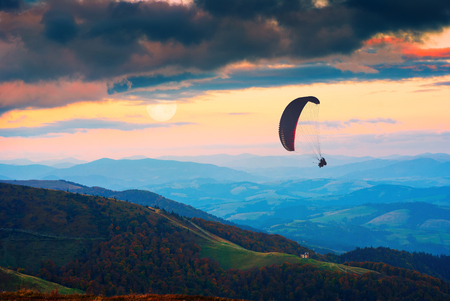 paraglide: Silhouette of flying paraglide in a sky above the misty valley. Moonrise in a clouds.