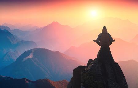 Silhouet van mensen mediteren in zittende yoga positie op de top van de berg boven de mistige vallei. Zen, meditatie, vrede