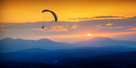 Paraglide silhouette in a light of sunrise above the misty Crimea valley. Vintage colors