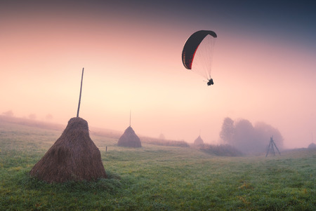 paraglide: Paraglide silhouette in a light of sunrise above the misty valley with haystacks on a hill. Stock Photo