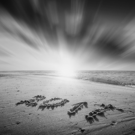 Year 2017 written in sand on a sea beach. Majestic sunrise with beautiful clouds in a sky. Monochrome colors. Stock Photo