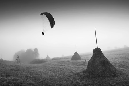 paraglide: Paraglide silhouette in a light of sunrise above the misty valley with haystacks on a hill. Monochrome colors.
