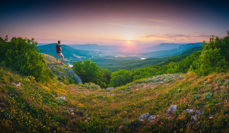 Hiker standing on a hill and enjoying the sunset in a Crimea mountain valley Stock Photo