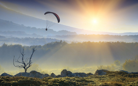 Silhouette of flying paraglide in a light of sunrise above the mountain valley. Stock Photo
