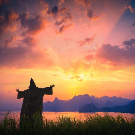 sotana: Silueta de cura con las manos levantadas sobre una colina contra el cielo del atardecer sobre el mar con espectaculares coloridas nubes. Foto de archivo