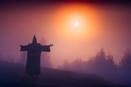 sotana: asistente de hadas en una sotana negro de pie en una colina y bienvenidos elevar sol sobre el valle de niebla. Foto de archivo