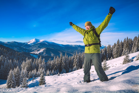 offset views: Hiker man standing with raised hands achieving the top, against winter mountain landscape. Happy tourist in winter. Carpathians, ukraine, Europe.