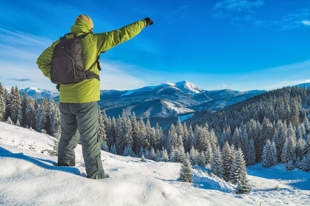 offset views: Winner standing with raised hand on a hill covered with snow, against winter mountain landscape. Champion on a top. Carpathians, ukraine, Europe. Stock Photo