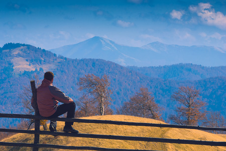 contemplates: Man sitting on a wooden fence and contemplates the carpathian mountain valley. Carpathians, Ukraine, Europe. Stock Photo