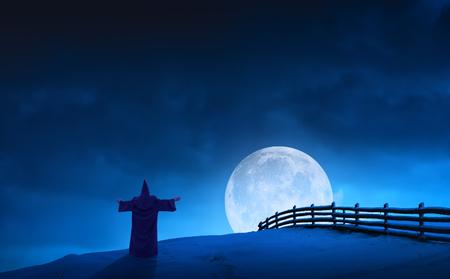 sotana: Silueta del mago de hadas que se coloca en una colina de la nieve y da la bienvenida al levantamiento de la Luna Llena en un valle. Humor navideño. Paisaje nocturno. Foto de archivo