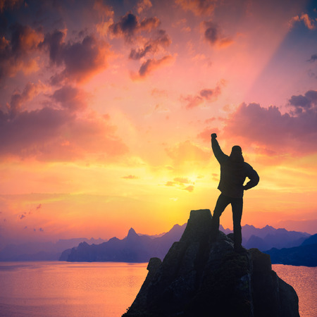 rejoices: Winner man standing on a rocks edge with raised hand and rejoices red sunset above the sea.