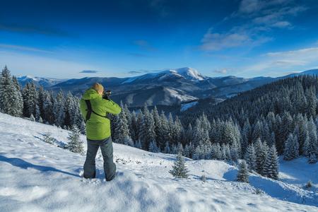 Photographer with photo camera, taking photos of beautiful winter mountain landscape. Carpathians, Ukraine, Europe