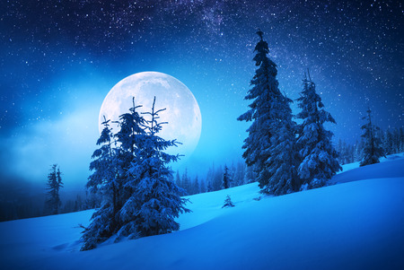 Majestic moon rise in a winter forest covered with fresh snow. Fantastic milky way in a starry sky. Christmas night.