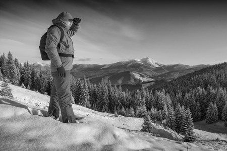 offset views: Hiker standing on a hill covered with snow against winter mountain landscape and looking to the horizon. Backpacker on a top. Black and white. Stock Photo