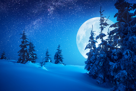 Full moon rising above the winter valley covered with fresh snow. Fantastic milky way in a starry sky. Christmas night. Stock Photo