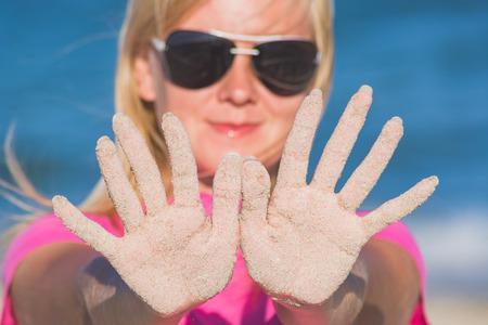 alzando la mano: Girl in sunglasses show hands covered with sand on a blue sea background.