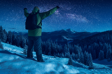 Hiker standing with raised hands against starry night sky with milky way above the winter mountain valley. Christmas night.