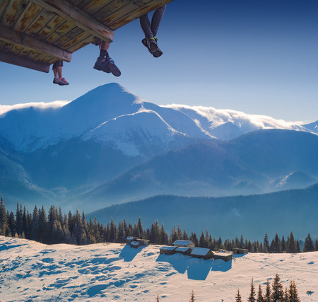 Hikers sit on a wooden flooring above the valley with wooden houses on a Carpathian snowy hill under highest Uktainian mountain Hoverla. Beautiful winter landscape. Ukraine, Europe