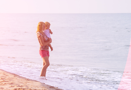 holyday: Mother and daughter playing on the beach. Bright holyday mood. Concept of happy family.
