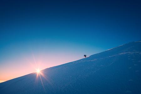 A climber climbs up a snowy slope. Sunset sky on a horison.