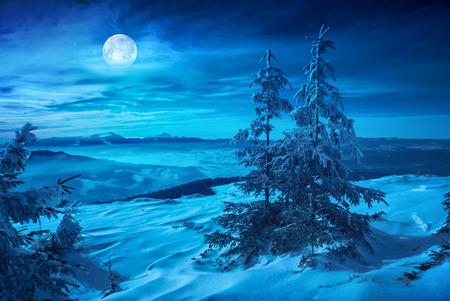 Levée de la pleine lune au dessus de la vallée de montagne hivernale recouverte de neige fraîche. Paysage de nuit. Banque d'images - 72421026