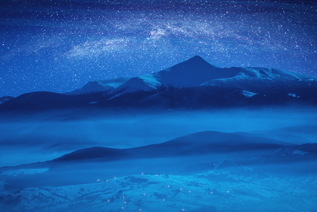 Starry sky with milky way above high mountain covered with snow. Fantastic winter night. Stock Photo