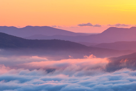 Sunset in a Crimea mountain valley covered with low clouds. Ukraine, Europe.