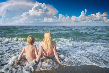 Mother with son sitting on sandy beach in a water and enjoy the seascape. Summer holidays, vacation concept.