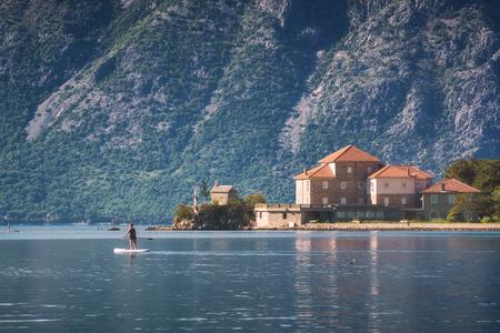 Houses on a coast of Boka Kotor bay. Man on a boat. Montenegro, Europe.