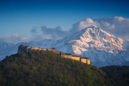 Rasnov Citadel, historic monument and landmark in Romania against high mountain in a sunset light.