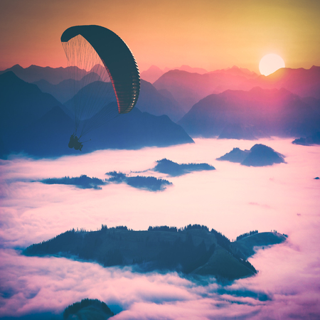 Paraglide silhouette in a light of sunrise above the misty mountain valley.