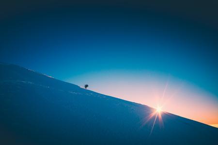 A climber climbs up a snowy slope. Sunset sky on a horison. Instagram stylisation.