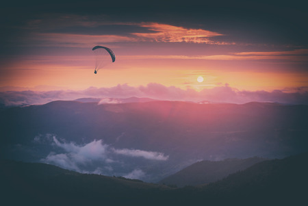 Paraglide silhouette against the sunset sky, flying over the mountain valley. Instagram stylisation.
