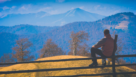 Man sitting on a wooden fence and contemplates the carpathian mountain valley. Instagram stylisation. Banco de Imagens