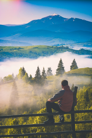 Man sitting on a wooden fence in a carpathian mountain valley covered with morning fog. Instagram stylisation. Stok Fotoğraf