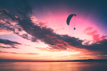 man flying: Paragliding silhouette in a light of majestic sunset flying above the sea.